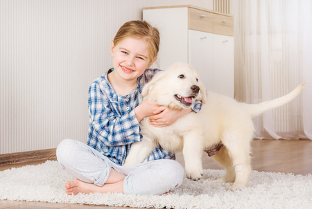 Smiling little girl hugging cute fluffy retriever puppy at home