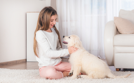 Teenage girl lying with cute fluffy retriever puppy on carpet