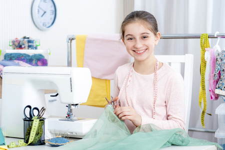 smiling little girl seamstress working at the sewing machine and smiling