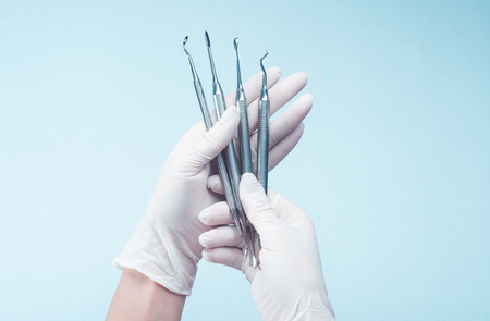 Hands in gloves holding medical tools on light Foto de archivo