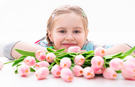 Young smiling kid with magnificent bouquet of creamy spring flowers, isolated