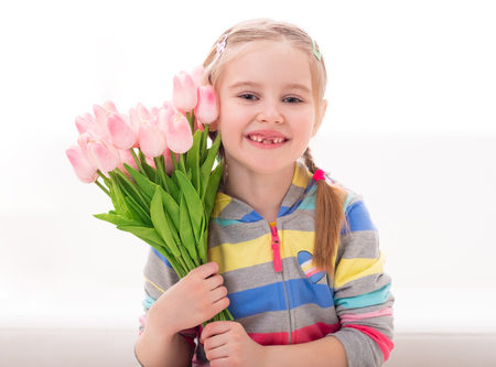 Cheerful beatiful little girl with a armful of colorful flowers, on white background
