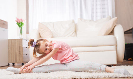 Motivated child doing hard stretches at home, in the living room