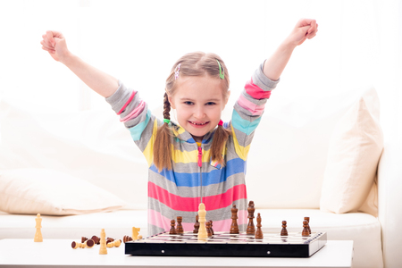 Adorable school age girl feels extremely happy about winning in chess