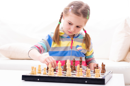 Cute small girl is hardly concentrated, when plating chess game