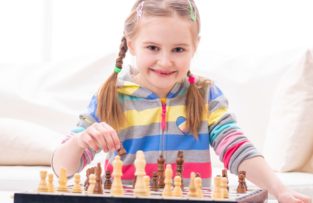 Cheerful smiling little girl is playing chess at amateur level Фото со стока