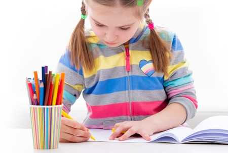 Cute schoolgirl coloring her interesting study book