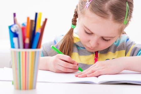 Adorable young female pupil carefully working in her copybook, on white background Фото со стока