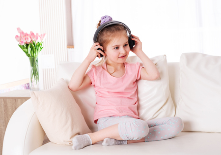 Preteen child enjoys listening to modern music on the couch
