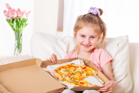 Smiling little girl eating pizza, on the couch