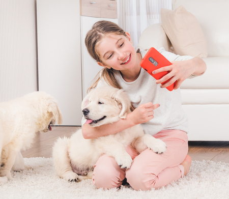 Teenage girl taking selfie with cute retriever puppies
