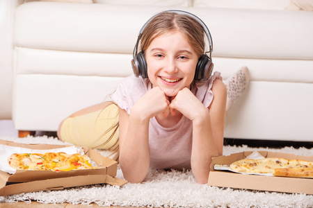 Cute teenage girl enjoy her leisure with tasty pizza and nice music