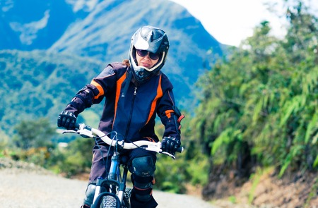 Girl in special suit and equipment riding a bike on the background of mountains