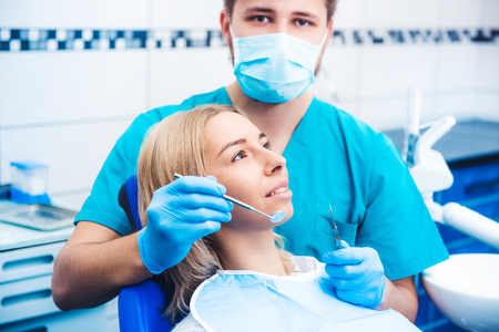 Dentist examinating blond girl with tools Фото со стока