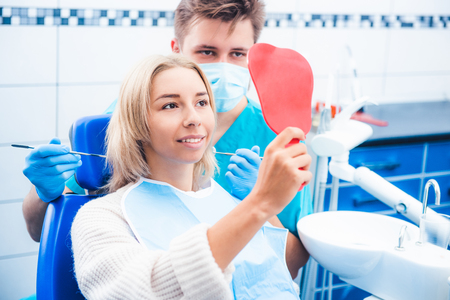 Blond girl and dentist looking into red mirror Фото со стока
