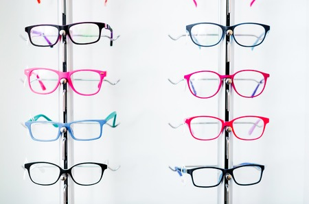 Different colorful glasses for kinds on the showcase in the optical store Banque d'images - 123993123