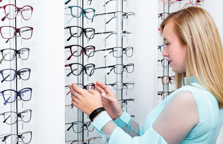 Teenage girl chooses glasses with showcase in the optical store