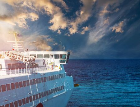 Floating cruise ship with mountains on background at sunset