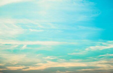 Light blue sky background with tiny fluffy clouds