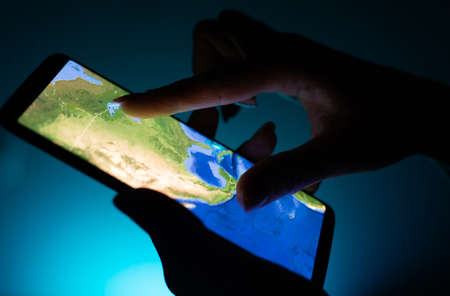 Kharkiv, Ukraine - 16 November 2018: close up girl hand using tablet with Google map app on smartphone screen with a dark background Editorial