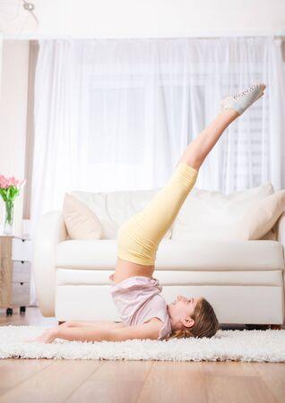 Active girl posing, raising legs up at carpet in living room