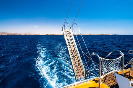Small fishing boat alone in deep blue sea with sunny beach at horizon