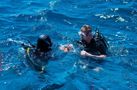 Two professional scuba divers making gestures at sea surface