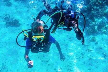 plongeurs s'entraînant sous l'eau près des récifs coralliens