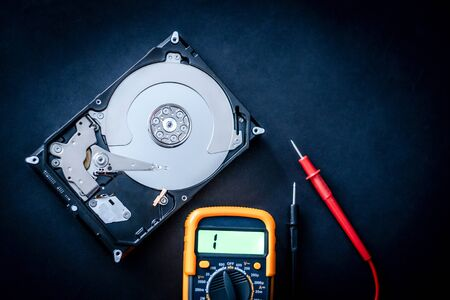 Repair of open computer hard disk drive and usage of digital multimeter, closeup with text space