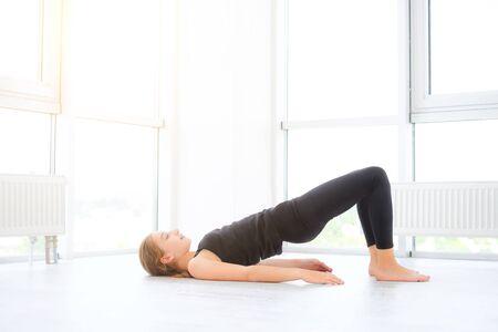 Hübsches junges Mädchen, das Übungen auf einem Boden im weißen Raum macht
