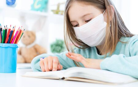 Cute Schoolgirl In Medical Face Mask Studying At Home Stock Photo ...