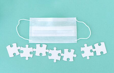Medical mask and jigsaw puzzle pieces with copy space