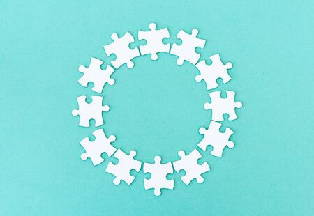 Circle made of white jigsaw puzzle pieces on blue