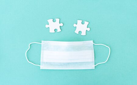 Two empty jigsaw puzzle pieces near medical mask Archivio Fotografico