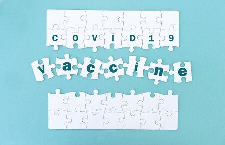 Jigsaw puzzle pieces with coronavirus vaccine, blue background