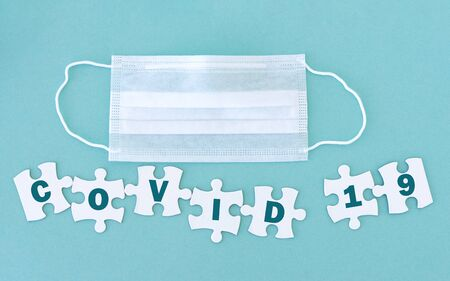 Medical mask and jigsaw puzzle pieces with text Covid 19