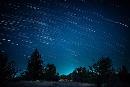 Colorful startrails above dark forest Фото со стока