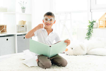 Happy little boy reading book with glasses on stick in childrens room