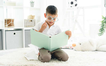 Cute little boy reading nice book wearing paper glasses indoors
