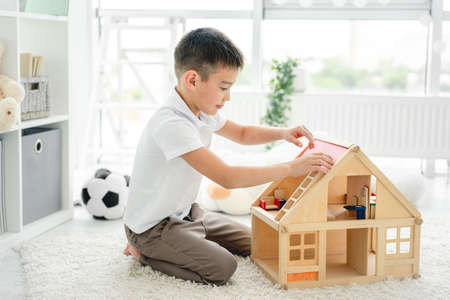 little boy playing alone with wooden house in kids room