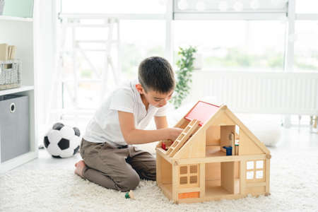 little boy playing alone with wooden house in kids room Stock Photo