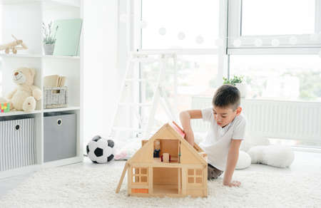 Cute little boy playing alone with wooden house in childrens room