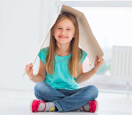 School girl plays with cardboard making it her roof Standard-Bild