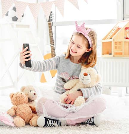 Cute little girl taking selfie with teddy bear in light room Imagens