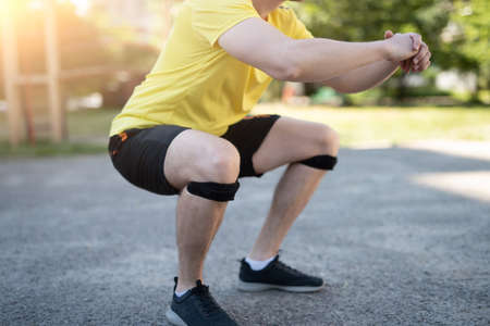 Man doing squat in knee support bandage during street workout