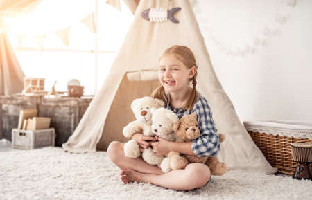 Happy little girl playing with teddy bears in room with wigwam in kids room Reklamní fotografie