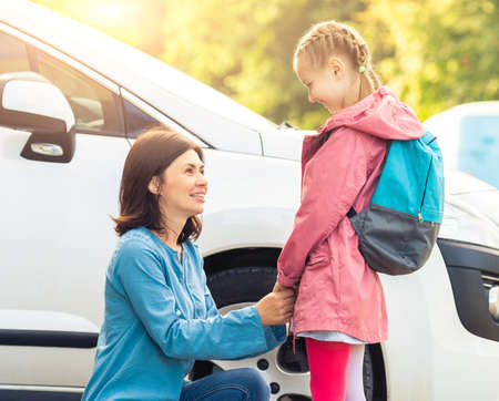 Mother taking little girl back to school on white car background