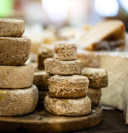 Goat cheese heads stacked on wooden plate