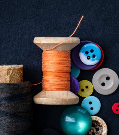 Colorful sewing buttons and orange thread spool macro