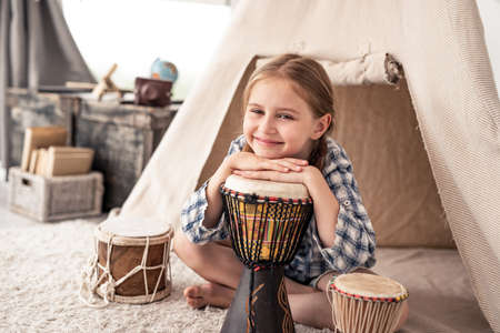 Cute little girl with ethnic drums sitting near wigwam in playroom